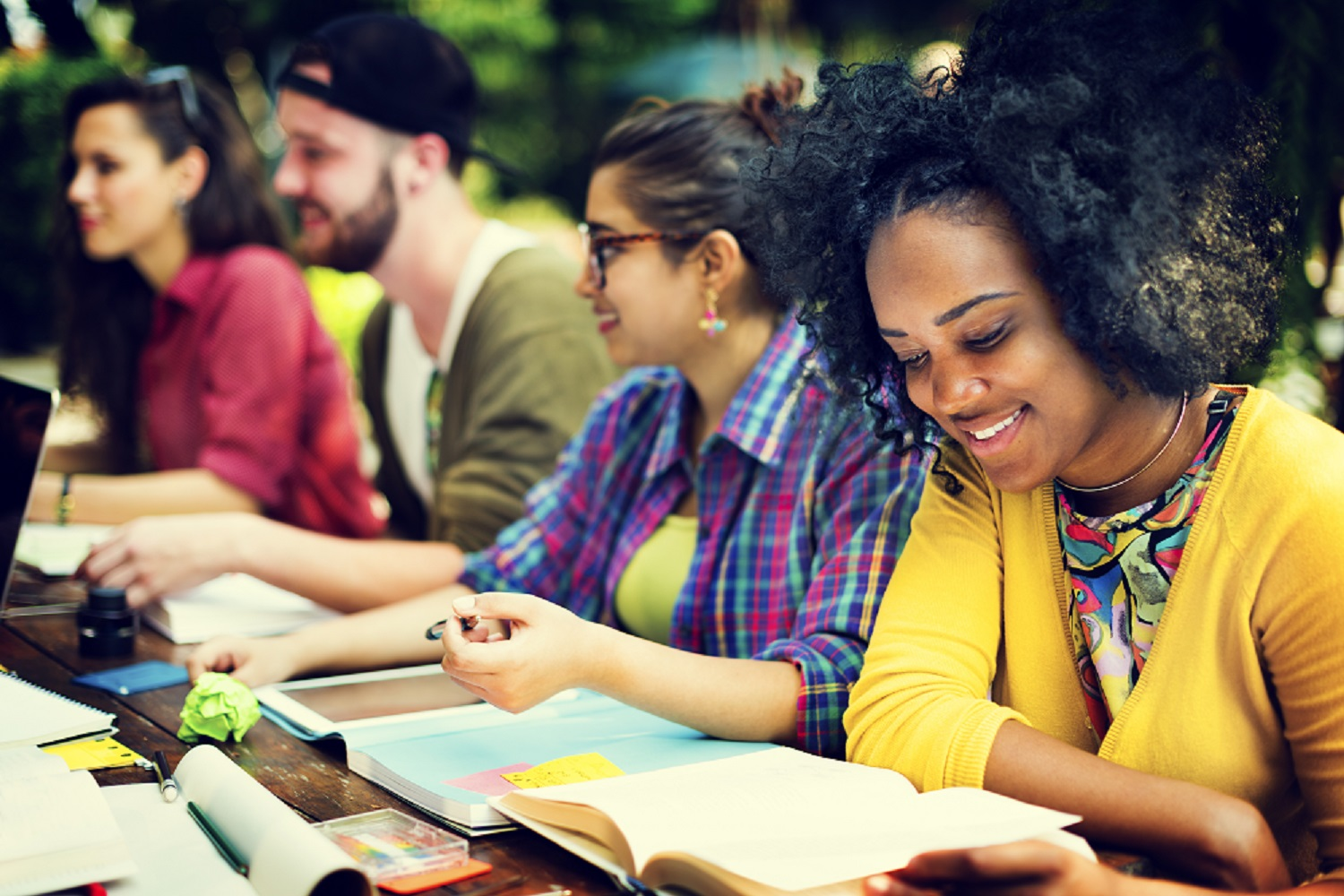 Teens-college-students-group-smiling-reading-yellow-jed